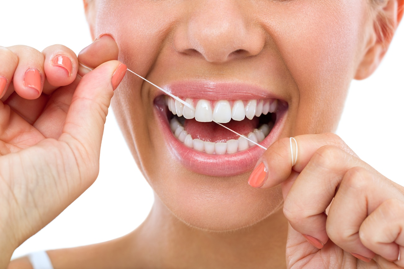 Young woman flossing her teeth , close up , isolated on white background