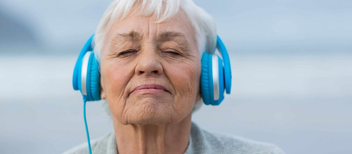 Woman listens to headphones while wearing hearing aids