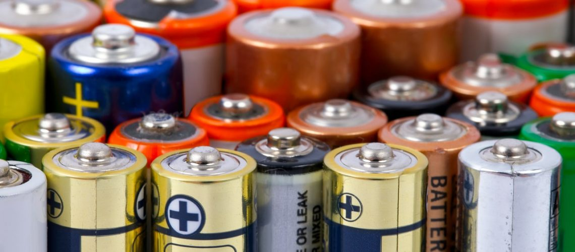 Many AA sized batteries on white