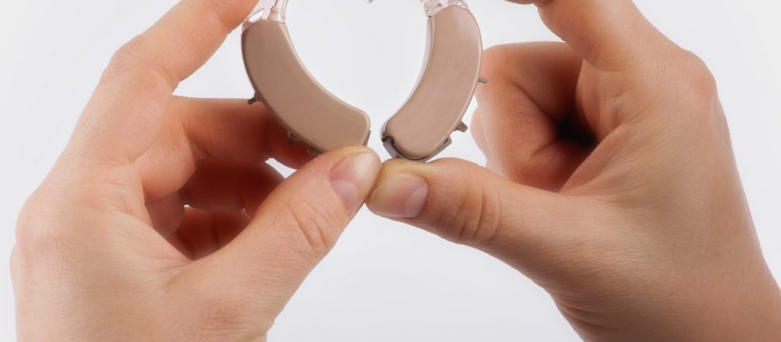 Hands forming a heart shape from hearing aids