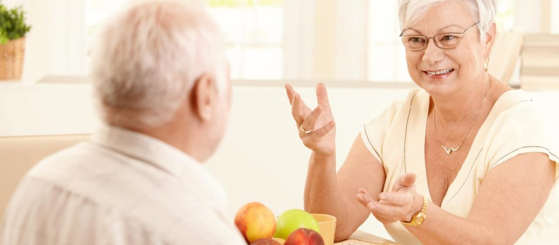 Elderly cheerful wife chatting to husband at breakfast table, gesturing, smiling.